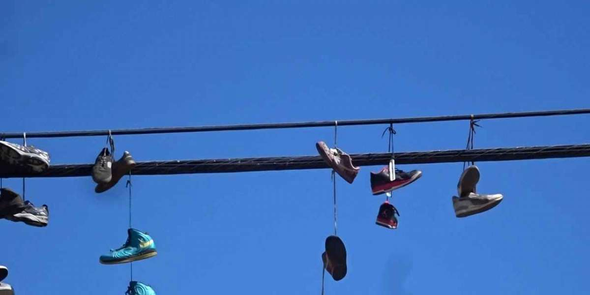Why are there shoes on power lines and why do people Throw shoes over power lines.